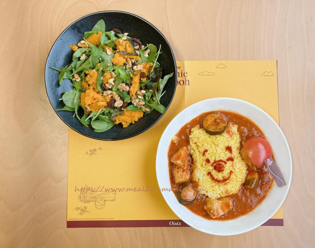くまのプーさんのトマトカレーとサラダが特製ランチョンマットの上にある